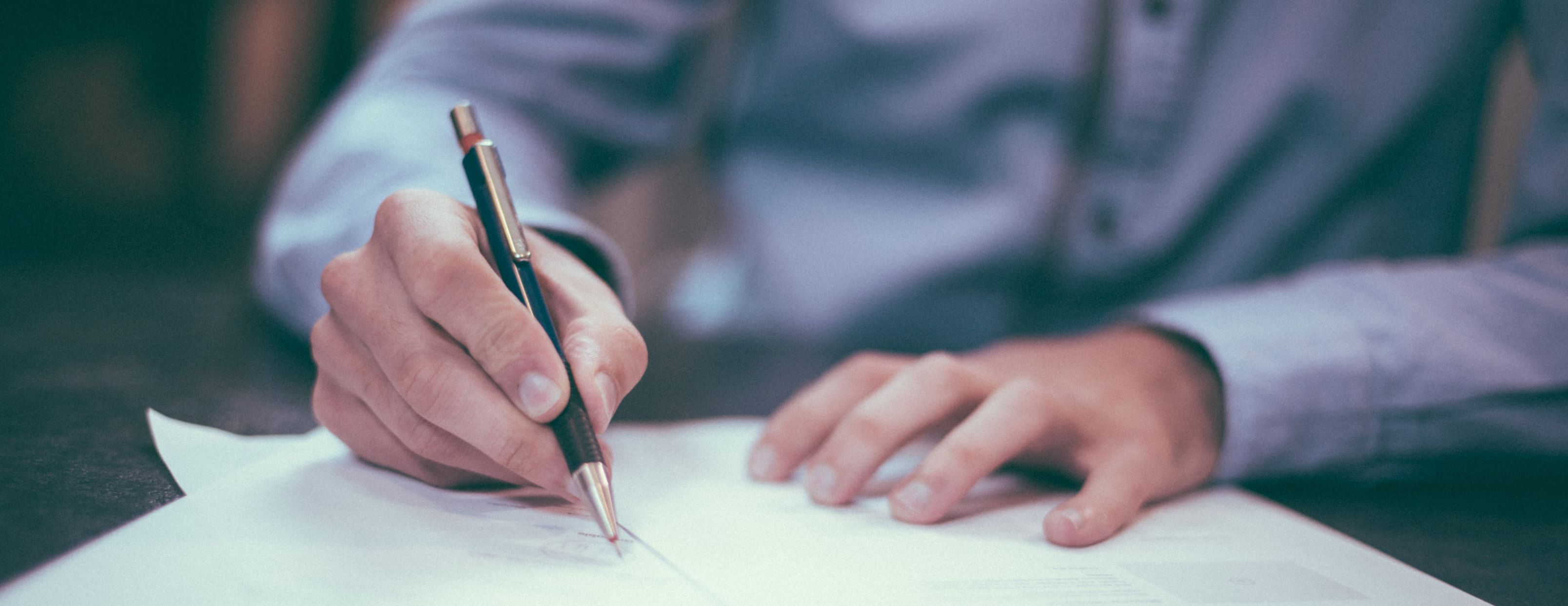 A photo of a man weaing a smart shirt holding a pen and signing a document