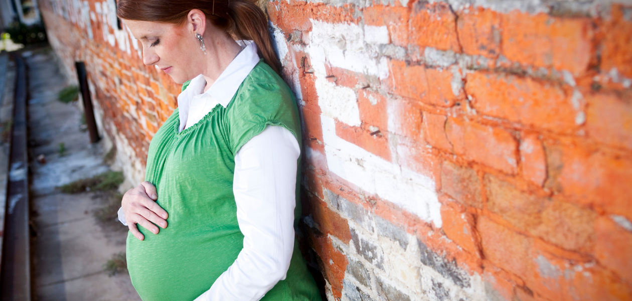 Heavily pregnant women with red hair stands against a wall holding her bump