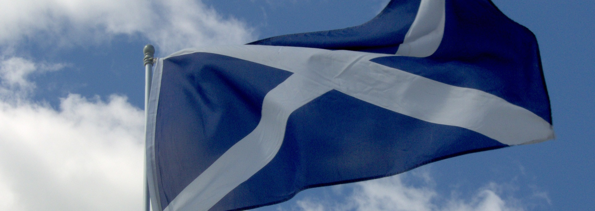 St Andrews cross Scottish flag flying against a blue sky with clouds