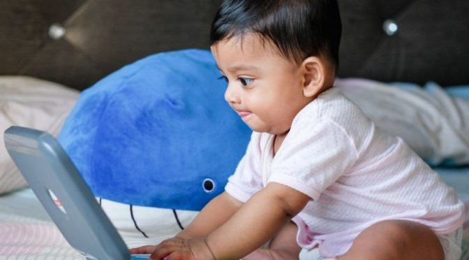 Baby sat on bed playing with a laptop