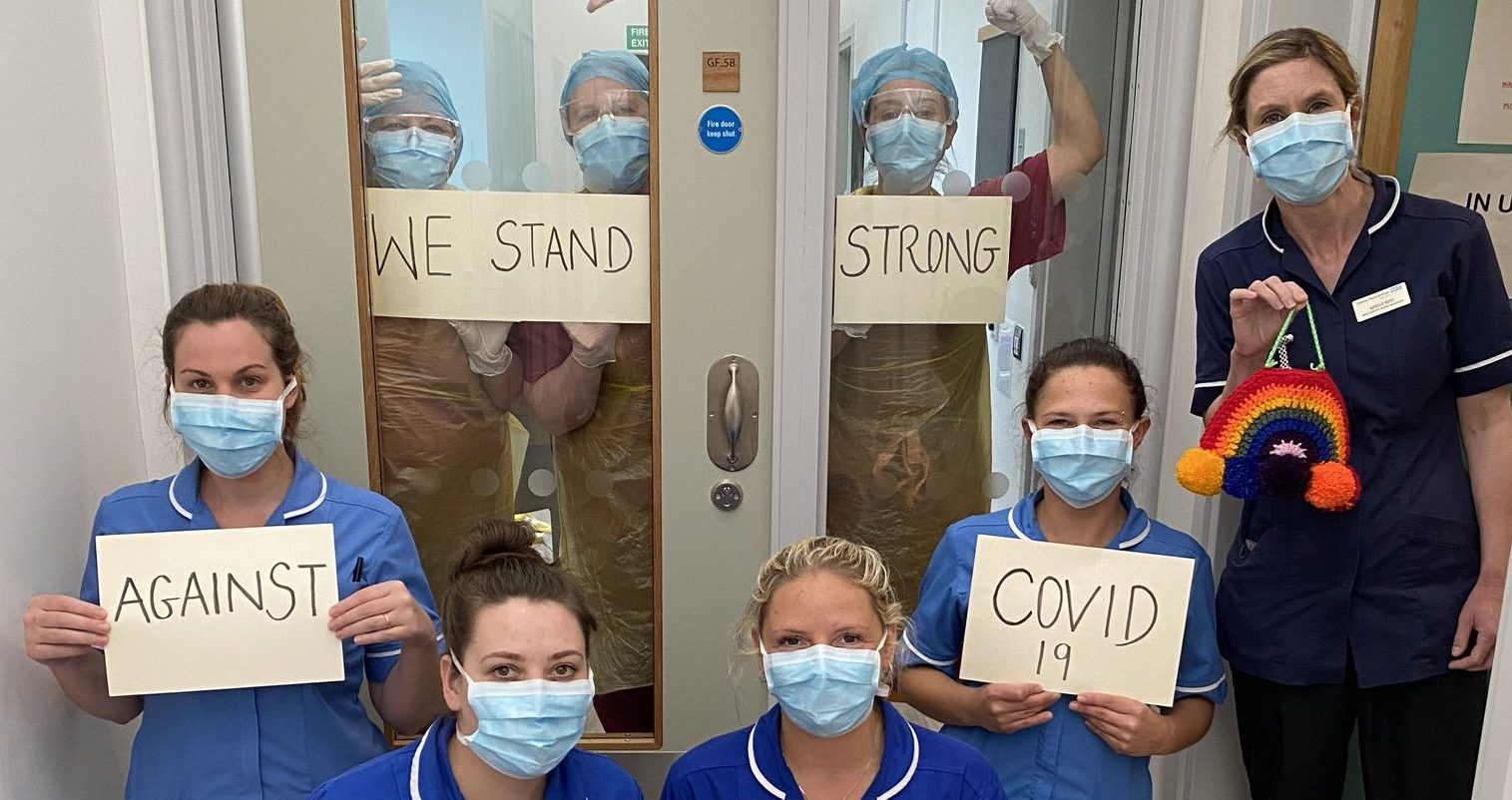 Specialist MBU staff at Jasmine Lodge holding signs saying We stand strong against COVID-19""